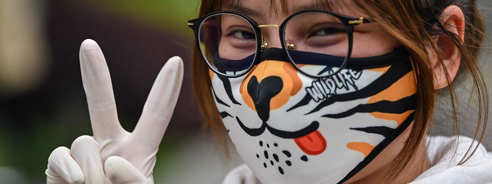 Eine junge Chinesin trägt eine ausgefallene Gesichtsmaske.