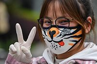 A woman wearing a face mask gestures on a street in Wuhan, China's central Hubei province on April 3, 2020. - Wuhan, the central Chinese city where the coronavirus first emerged last year, partly reopened on March 28 after more than two months of near total isolation for its population of 11 million. (Photo by Hector RETAMAL / AFP)
