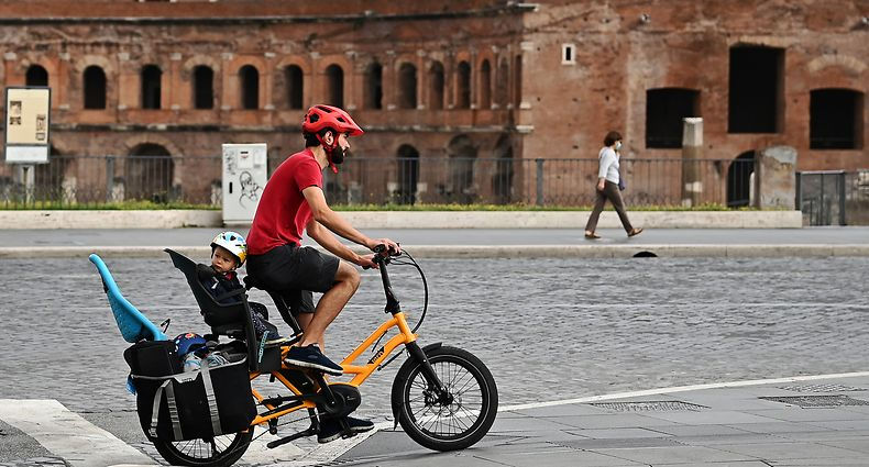 A man rides a bicycle with a toddler across Via dei Fori Imperiali in central Rome on June 17, 2020, as the country eases its lockdown aimed at curbing the spread of the COVID-19 infection, caused by the novel coronavirus. (Photo by Vincenzo PINTO / AFP)