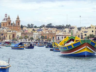 Traditional Maltese coloured fishing boats luzzu in Marsaxlokk harbour, Malta
