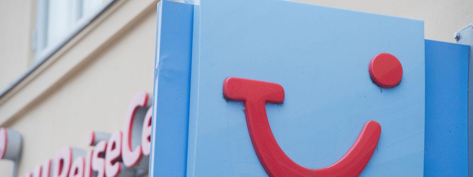 An einem Reisebüro hängt das Firmen-Schild mit dem Logo des Reiseveranstalters Tui.