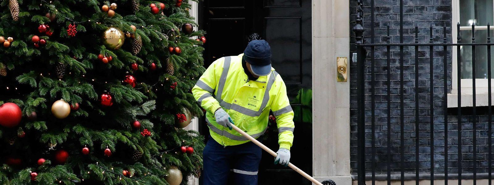 Un travailleur balaie les feuilles sur le parvis du 10, Downing Street à Londres, adresse du Premier ministre anglais.