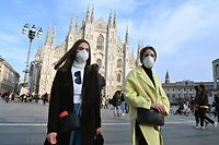 TOPSHOT - Woen wearing a respiratory mask walk across Piazza del Duomo in central Milan on February 23, 2020. - Tens of thousands of Italians prepared for a weeks-long quarantine in the country's north on February 23 as nerves began to fray among the locals faced with new lockdown measures. (Photo by ANDREAS SOLARO / AFP)