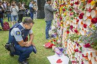 ARCHIV - 18.03.2019, Neuseeland, Christchurch: Ein Polizist kniet nieder, um einige der Botschaften zu lesen, die auf einem behelfsmäßigen Denkmal für die Opfer der Anschläge von Christchurch an der University of Canterbury hinterlassen wurden. (zu «Christchurch-Attentäter: Behörden prüfen Aufenthalt in Deutschland» Foto: Pj Heller/ZUMA Wire/dpa +++ dpa-Bildfunk +++