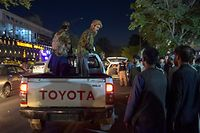 EDITORS NOTE: Graphic content / Taliban fighters stand on a pickup truck outside a hospital as volunteers bring injured people for treatment after two powerful explosions, which killed at least six people, outside the airport in Kabul on August 26, 2021. (Photo by WAKIL KOHSAR / AFP)