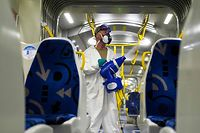 A worker wearing a protective suit and mask, disinfects a tramway at the Solea transport depot in Mulhouse, eastern France, on May 20, 2020, as France eases lockdown measures taken to curb the spread of the COVID-19 pandemic, caused by the novel coronavirus. (Photo by SEBASTIEN BOZON / AFP)