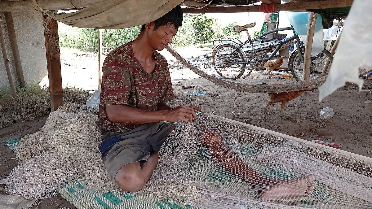 Fischer Ho San arbeitet an einem seiner Fischernetze.