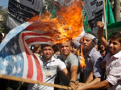 Palestinian Hamas supporters burn a make-shift US flag during a protest in Gaza City on Friday