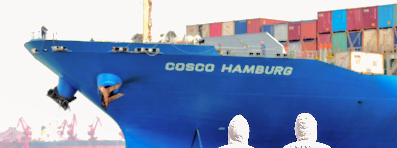 China fährt die Produktion wieder hoch: Zwei Kontrolleure in Schutzanzügen im Hafen von Shandong.