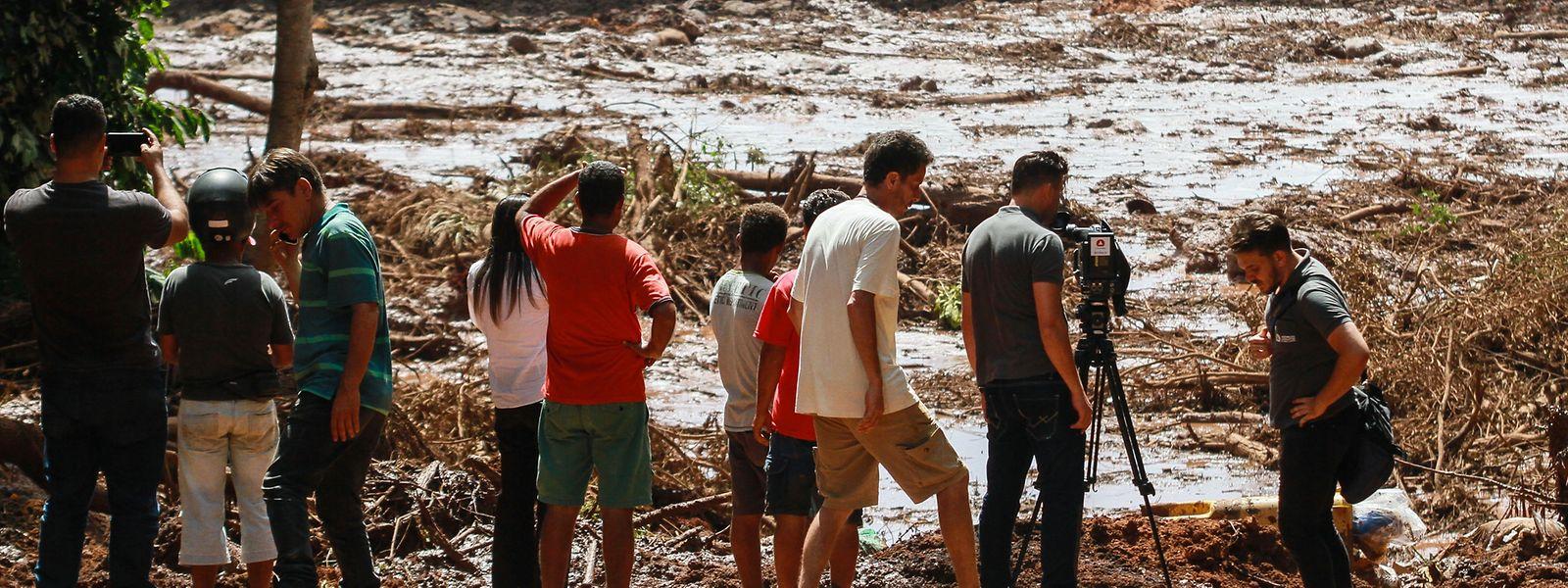 Menschen beobachten die Schlammmassen nach dem Bruch eines Staudamms an der Feijão Eisenerzmine.