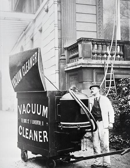 Hausarbeit im Jahr 1900: Der Staubsauger ist so groß, dass er von mehreren Personen oder sogar mit Hilfe eines Pferdes von Haus zu Haus gezogen werden muss.