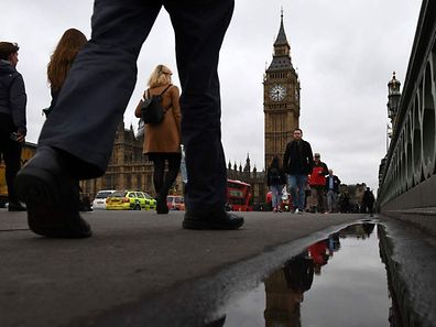 Commuters walks over Westminster bridge by the Houses of Parliament in central London.