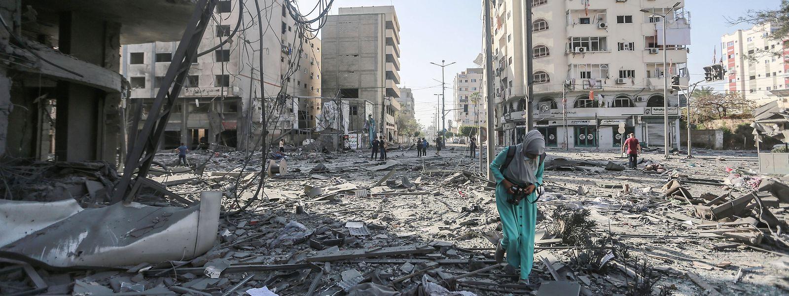 Eine Fotografin geht durch die Trümmer des schwer beschädigten Al-Jawhara-Turm, nachdem der Turm von israelischen Luftangriffen getroffen worden war.