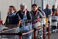 Costumers waits at the entrance of a supermarket in Forville on March 18, 2020 as a strict lockdown is to come into effect to stop the spread of the COVID-19, caused by the novel coronavirus. - Belgians must stay at home from midday on March 18, 2020 until at least April 5 to prevent the spread of the coronavirus, Prime Minister Sophie Wilmes said on March 17. The only residents allowed out will be those needing medical attention, getting exercise or working in some businesses deemed essential, such as food markets and pharmacies, she said. (Photo by JOHN THYS / AFP)