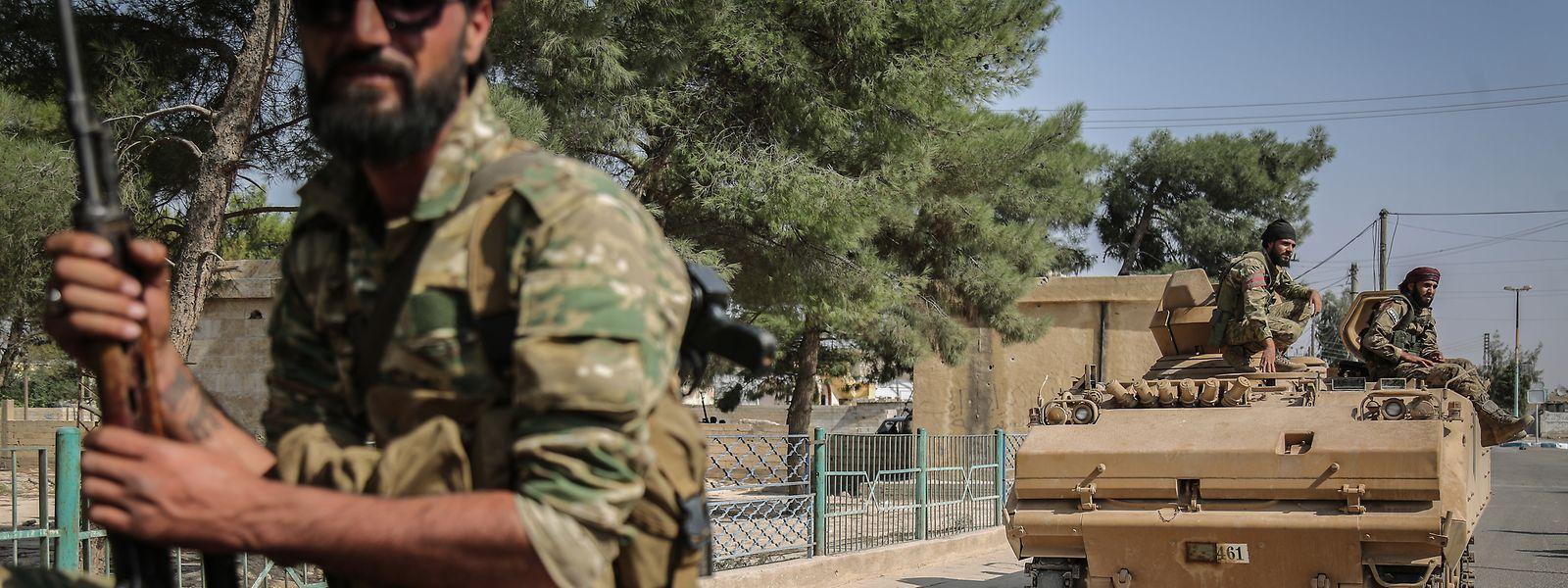 Soldaten der syrischen Nationalarmee patrouillieren nach Zusammenstößen mit kurdischen Soldaten mit einem Panzer auf einer Straße.