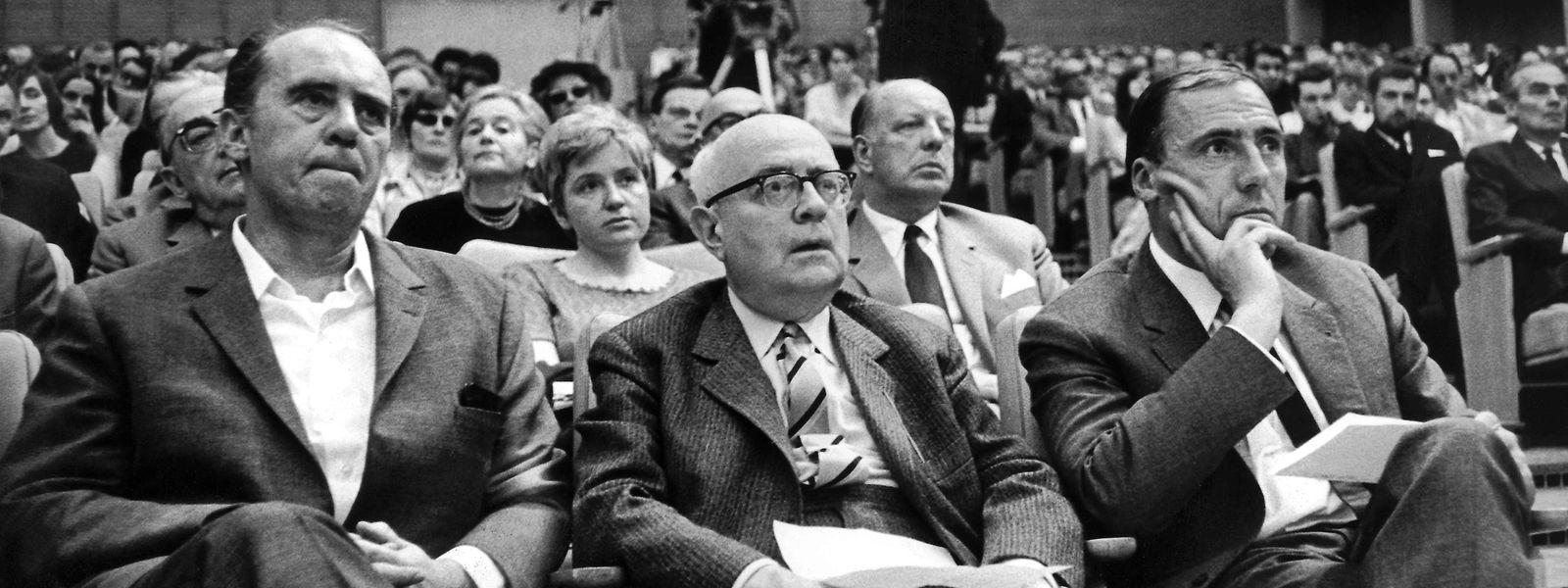 1968: Der Schriftsteller Heinrich Böll, der Soziologie-Professor Theodor W. Adorno und der Verleger Siegfried Unseld hören bei einer Veranstaltung gegen die Notstandsgesetzgebung im Großen Sendesaal des Hessischen Rundfunks einem Vortrag zu. Adorno ist am 6. August vor 50 Jahren gestorben.