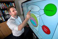 Thorsten Lehr, Saarbrücker Pharmazie-Professor vor einem Bildschirm mit einer von ihm entwickelten Simulation der Corona-Entwicklung.
