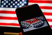 ARCHIV - 13.08.2020, Indonesien, Makassar: Abzeichen für die Präsidentschaftswahl mit den Aufschriften «Vote» und «2020» sind auf einem Smartphone-Bildschirm vor einer US-Amerikanischen Flagge zu sehen. (zu dpa Themenpaket zur US-Wahl) Foto: Herwin Bahar/ZUMA Wire/dpa +++ dpa-Bildfunk +++