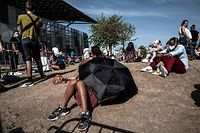 TOPSHOT - A man rests under an umbrella as people queue to get tested for Covid-19, on September 11, 2020 in Venissieux, near Lyon, amid the novel coronavirus pandemic. (Photo by JEFF PACHOUD / AFP)