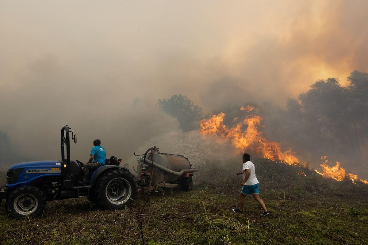 Bombeiros e populares combatem o incêndio que deflagrou ao início da tarde junto à aldeia de Pisão, em Barcouço, e obrigou ao corte da auto-estrada A1, Mealhada, 10 de agosto de 2017. PAULO NOVAIS/LUSA