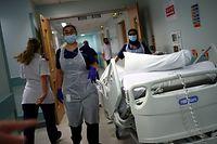 ARCHIV - 17.05.2020, Großbritannien, Blackburn: Medizinische Mitarbeiter des Royal Blackburn Lehrkrankenhaus in Schutzkleidung schieben einen Patienten auf einem Krankenhausbett durch einen Korridor. (zu dpa «Mehr als 200000 Corona-Todesfälle im Europäischen Wirtschaftsraum») Foto: Hannah Mckay/PA Wire/dpa +++ dpa-Bildfunk +++