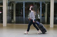A passnger wearing a facemask arrives at the Eurostar terminal at St Pancras station in London on May 6, 2020 as life continues under a nationwide lockdown imposed to slow the spread of the novel coronavirus. - Cross-Channel train operator Eurostar on May 2 said face masks covering the mouth and nose would be compulsory on services between London, Paris and Brussels from May 4. Britain's death toll from the coronavirus has topped 32,000, according to an updated official count released May 5, pushing the country past Italy to become the second-most impacted after the United States. (Photo by ISABEL INFANTES / AFP)