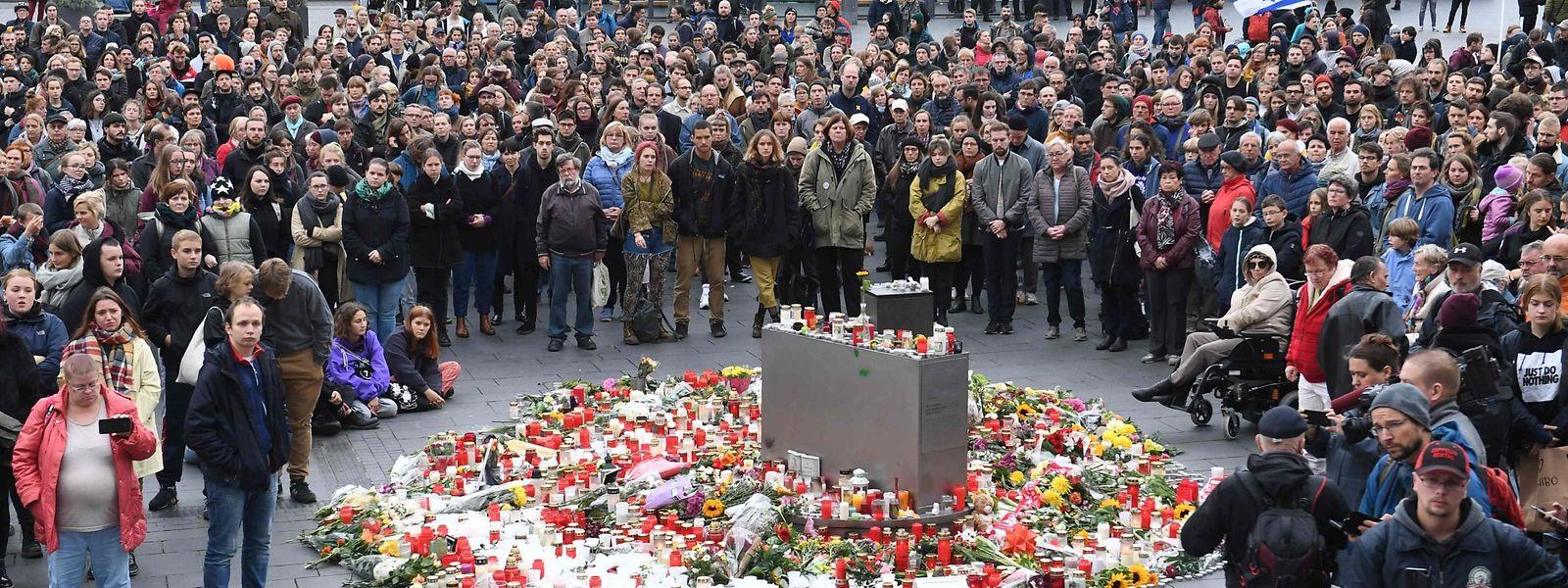 Teilnehmer der Demonstration des Bündnisses «Halle gegen Rechts - Bündnis für Zivilcourage» versammeln sich auf dem Marktplatz hinter abgelegten Blumen und Kerzen.