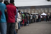 (FILES) In this file photo taken on November 24, 2018 Central American migrants -mostly from Honduras- wanting to reach the United States in hope of a better life, line up for food outside a shelter in Tijuana, Baja California State, Mexico, near the US-Mexico border fence. - President Donald Trump on November 24, 2018 announced migrants seeking asylum in the United States via its southern border would need to wait in Mexico while their claims are processed, appearing to confirm a report regarding a new bilateral deal. (Photo by Pedro PARDO / AFP)