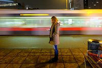 Woman standing alone on city street and checking her smartphone at night. Driving tram in background.