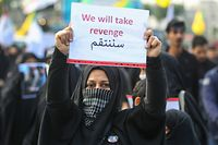 """TOPSHOT - An Iraqi woman holds a placard during the funeral of Iranian military commander Qasem Soleimani, Iraqi paramilitary chief Abu Mahdi al-Muhandis and eight others in Baghdad's district of al-Jadriya, in Baghdad's high-security Green Zone, on January 4, 2020. - Thousands of Iraqis chanting """"Death to America"""" joined the funeral procession for Iranian commander Qassem Soleimani and Iraqi paramilitary chief Abu Mahdi al-Muhandis, both killed in a US air strike. The cortege set off around Kadhimiya, a Shiite pilgrimage district of Baghdad, before heading to the Green Zone government and diplomatic district where a state funeral was to be held attended by top dignitaries. In all, 10 people -- five Iraqis and five Iranians -- were killed in Friday morning's US strike on their motorcade just outside Baghdad airport. (Photo by AHMAD AL-RUBAYE / AFP)"""