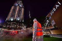 A municipal worker disinfects the streets as a preventive measure against the spread of COVID-19 (novel cornavirus), as the Burj Khalifa is seen in the background, in downtown Dubai, on March 27, 2020. - The United Arab Emirates, of which Dubai is a member, has imposed a March 26 to 29 nightime lockdown to allow for outdoors and public transport sanitation operations, amid the outbreak of the new coronavirus. (Photo by GIUSEPPE CACACE / AFP)