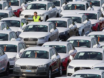 A worker walks among Audi A1 cars in the parking of the Audi powerplant in Brussels, Belgium September 28, 2015. Volkswagen, facing a scandal for the falsification of U.S. emissions tests has said 11 million cars worldwide had defeat devices installed, including 2.1 million of Audi of models A1, A3, A4, A5, A6, TT, Q3 and Q5.  REUTERS/Yves Herman