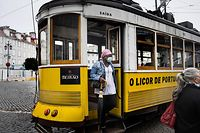 A woman wearing a face mask gets off a tram in downtown Lisbon on October 28, 2020. - The Portuguese support the wearing of the compulsory mask outdoors, a measure that came into force today, in order to stem the resumption of the coronavirus epidemic. (Photo by PATRICIA DE MELO MOREIRA / AFP)