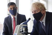 (FILES) In this file photo taken on April 29, 2021 Britain's Chancellor of the Exchequer Rishi Sunak (L) watches as Britain's Prime Minister Boris Johnson, wearing a face covering due to Covid-19, looks through a microscope as he takes part in a science lesson at King Solomon Academy in London, on April 29, 2021. - Britain's Prime Minister Boris Johnson and Chancellor of the Exchequer Rishi Sunak have both been designated a close contact of a person infected with Covid, Downing Street said July 18, 2021. The development came just as Johnson's government prepares to ditch most pandemic restrictions in England on July 19. Health Secretary Sajid Javid confirmed on July 17 he had tested positive for Covid-19 and was now self-isolating for 10 days. (Photo by Dan Kitwood / POOL / AFP)