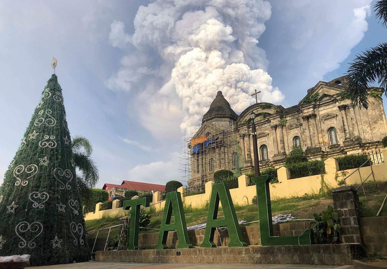 Die Aschewolke des Vulkans ist hinter der Kirche der Stadt Taal zu sehen.
