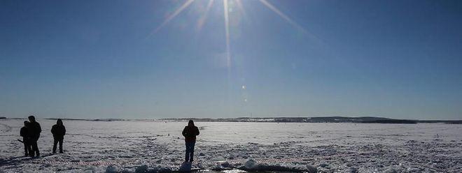 Leute betrachten ein großes Loch in einem gefrorenen See bei Tscheljabinsk. Über der Region war ein Meteoritenhagel niedergegangen.