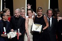 """French director Julia Ducournau (C) poses on stage with guests and laureates after she won the Palme d'Or for her film """"Titane"""" during the closing ceremony of the 74th edition of the Cannes Film Festival in Cannes, southern France, on July 17, 2021. (Photo by CHRISTOPHE SIMON / AFP)"""