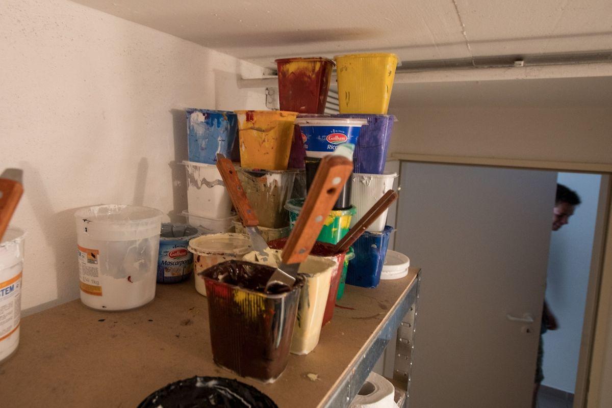 Farbbecher stapeln sich auf dem Regal in der Garage.