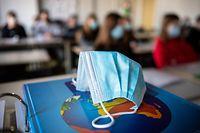 ARCHIV - 17.11.2020, Bayern, München: ILLUSTRATION - Ein Mund- und Nasentschutz liegt im Unterricht in einem Geographie-Seminar in der Jahrgangsstufe elf am staatlichen Gymnasium Trudering auf einem Weltalas, während im Hintergrund die Schülerinnen und Schüler mit Mund- und Nasenschutz zu sehen sind. Vor der nächsten Runde der Regierungschefs, bei der es auch um neue Corona-Regeln in Schulen gehen könnte, raten Experten bei Mund-Nasen-Bedeckungen auf das korrekte Tragen zu achten. (zu dpa «Experten: Gut sitzende Masken und Lüften für Schulunterricht wichtig») Foto: Matthias Balk/dpa +++ dpa-Bildfunk +++