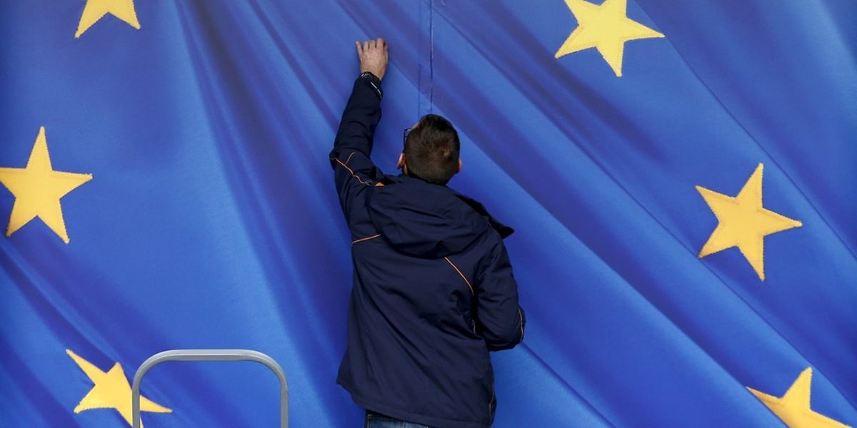 Un travailleur ajuste un autocollant géant à l'entrée de la Commission européenne à Bruxelles (28 octobre 2015).