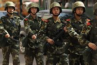 Chinese paramilatary police patrol on a street in Urumqi, capital of China's Xinjiang region on July 4, 2010 ahead of the first anniversary of bloody violence that erupted between the region's Muslim ethnic Uighurs and members of China's majority Han ethnicity. Urumqi was torn in two on July 5, 2009 as the Uighurs vented decades of unhappiness over Chinese rule with savage attacks on members of China's dominant Han. AFP PHOTO/Peter PARKS
