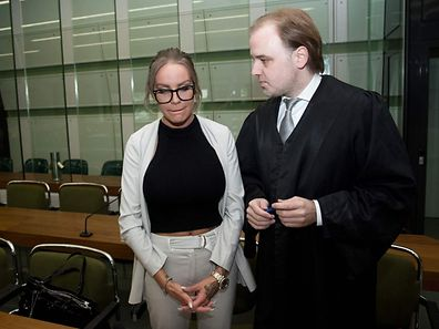German model Gina-Lisa Lohfink and her lawyer Burkhard Benecken arrive to the the District Court of Tiergarten in Berlin, on August 22, 2016.  Lohfink falsely accused two men of raping her and was sentenced to pay a fine for the false accusation. / AFP PHOTO / dpa / J�rg Carstensen / Germany OUT