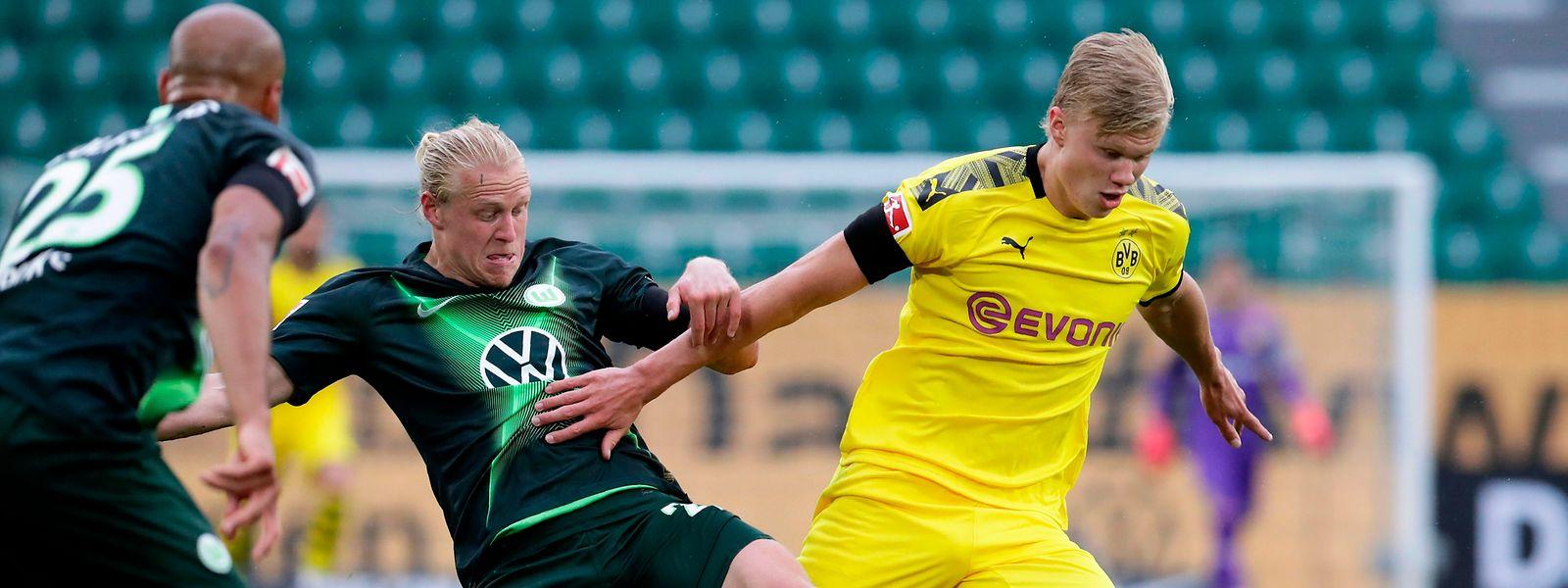 Wolfsburgs Xaver Schlager versucht, Dortmunds Erling Haaland (r.) den Ball abzunehmen.
