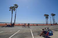04.05.2020, USA, Newport Beach: Menschen fahren auf dem Parkplatz nördlich des Newport Beach Pier mit dem Rad herum. Sport und Bewegung im Freien mit Abstand voneinander sind in Kalifornien erlaubt. Der US-Bundesstaat will strenge Auflagen für Geschäfte während der Corona-Krise schrittweise lockern. Foto: Jeff Gritchen/Orange County Register via ZUMA/dpa +++ dpa-Bildfunk +++