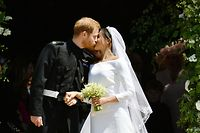 Britain's Prince Harry, Duke of Sussex kisses his wife Meghan, Duchess of Sussex as they leave from the West Door of St George's Chapel, Windsor Castle, in Windsor, on May 19, 2018 after their wedding ceremony. / AFP PHOTO / POOL / Ben Birchall