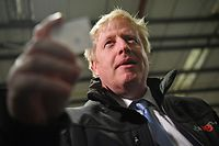 Britain's Prime Minister and Conservative party leader Boris Johnson reacts after reading the joke found inside one of the crackers during a visit to IG Design Group, wrapping paper designer and producer in Hengoed, south Wales on December 11, 2019, the final day of campaigning for the general election. - Britain will go to the polls tomorrow to vote in a pre-Christmas general election. (Photo by Ben STANSALL / POOL / AFP)