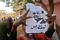 "A Sudanese protester carries a portrait of President Omar al-Bashir with Arabic writing that reads ""down and that is all"" during an anti-government demonstration east of the capital Khartoum on February 9, 2019. (Photo by - / AFP)"