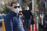 An Iranian man is pictured wearing a protective mask in Vanak square in the Iranian capital Tehran on March 2, 2020, following the COVID-19 illness outbreak, which Iran says has claimed 66 lives out of 1,501 cases of infection in the Islamic republic since February. - The novel coronavirus has sparked intense debate in Iran between ultra-conservative Shiite clerics and the government on how to most effectively tackle the deadliest outbreak of the disease outside China. (Photo by ATTA KENARE / AFP)