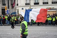"A protestor wearing ""yellow vest"" (gilet jaune) holds a French national flag on December 8, 2018 near the Arch of Triumph (Arc de Triomphe) in Paris during a protest against rising costs of living they blame on high taxes. - Paris was on high alert on December 8 with major security measures in place ahead of fresh ""yellow vest"" protests which authorities fear could turn violent for a second weekend in a row. (Photo by Eric FEFERBERG / AFP)"