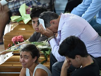Relatives mourn next to a coffin during a funeral service for victims of the earthquake, at a gymnasium arranged in a chapel of rest